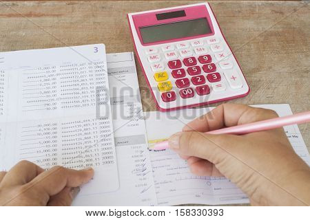 hand checking document monthly expense credit card with passbook bank and payment bill of bank