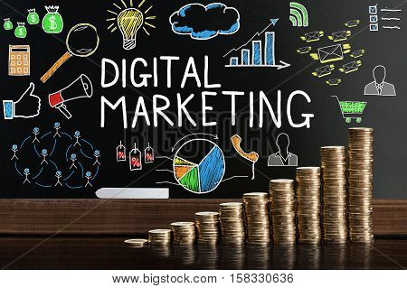 Stack Of Coins In Front Of Blackboard Showing Digital Marketing Concept