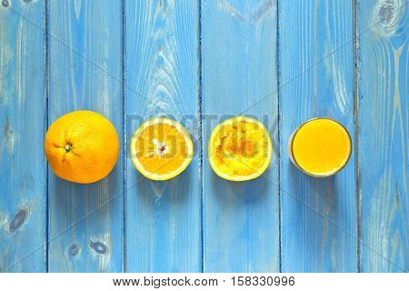 Freshly squeezed orange juice showing a wholehalfand a glass full on a blue wooden textured background