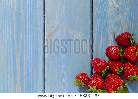 freshtastysweet strawberries on a textured blue wooden background