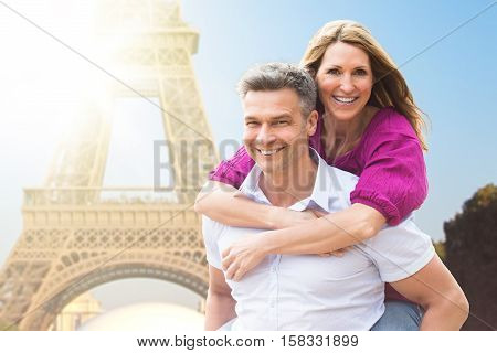 Portrait Of Happy Man Piggybacking His Wife Near Eiffel Tower