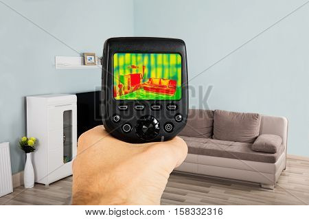 Close-up Of Person Hand Using Infrared Thermal Camera In Living Room At Home