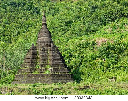 Small pagoda in Mrauk U the Rakhine State of Myanmar surrounded by lush foliage.