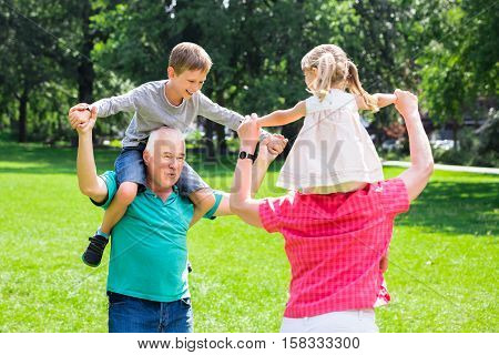 Happy Old Grandparents Enjoy Fun Piggyback Ride With Grandchildren Together In Park