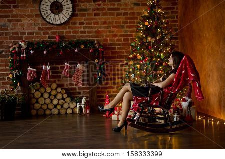 Elegantly dressed young woman sits in rocking-chair near Christmas-tree. She has thought or dozes. Room is specially decorated by Christmas. Hours over a fireplace. Under fir-tree there are lot of gifts