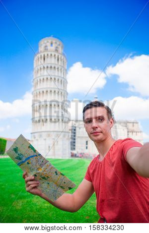 Young happy man with toristic map on travel to Pisa. Tourist traveling visiting The Leaning Tower of Pisa, Italy