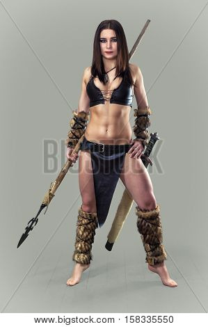 Beautiful athletic girl in the image of ancient warrior with a spear.
