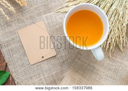 Orang juice and brown paper label with rice drying on sackcloth.Top view focus.