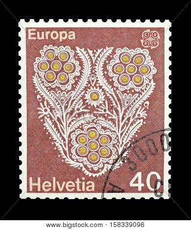 SWITZERLAND - CIRCA 1975 : Cancelled postage stamp printed by Switzerland, that shows Flower pattern of a cotton embroidery.