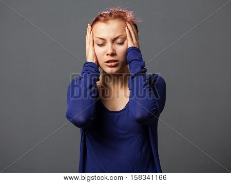 Young woman tormented by headache gray background