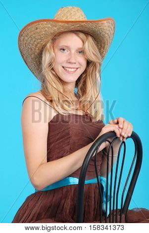 Pretty thirteen year old girls wearing a big floppy straw sun hat isolated on blue