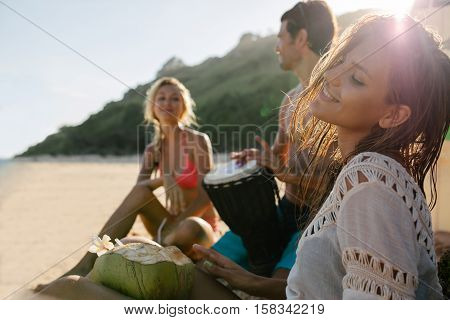 Young woman relaxing on the sea shore with her friends in background. Friends partying and having fun on the beach.