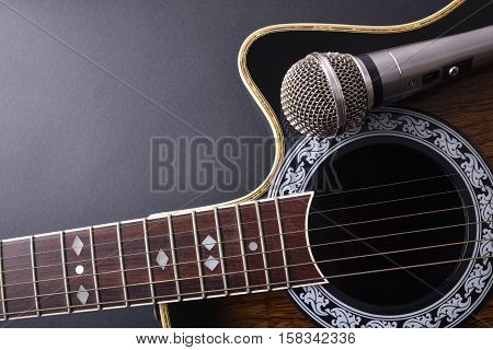 Acoustic Guitar And Microphone Isolated On Black Table Top