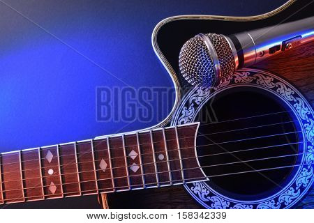 Acoustic Guitar And Microphone Isolated With Red And Blue Lights