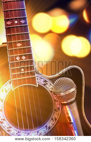 Acoustic Guitar And Microphone With Lights In The Background