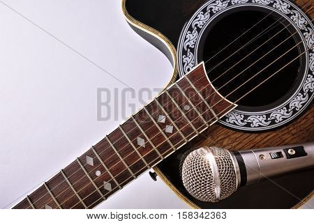 Acoustic Guitar And Microphone Isolated On White Table Top