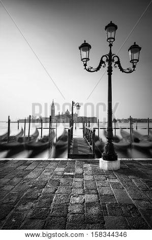Gondolas At Shoreline By Saint Mark Square With San Giorgio Di Maggiore Church In The Background, Ve
