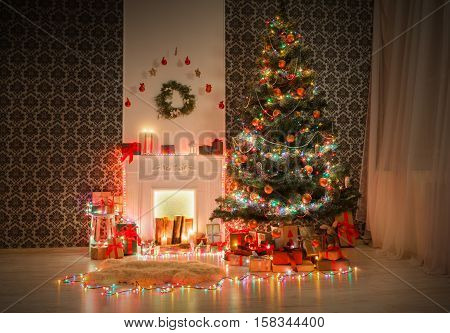Christmas living room illumination. Beautiful xmas lights garland, decorated christmas tree near fireplace. Modern interior design, magic atmosphere. Winter holidays night, candles and present boxes