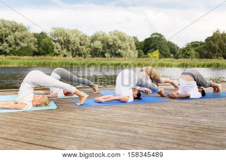 fitness, sport, yoga and healthy lifestyle concept - group of people making plow pose on mat outdoors on river or lake berth