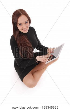 Happy student teenage girl sitting on the floor with tablet pc isolated on white