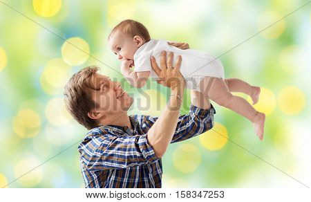 family, fatherhood and parenthood concept - happy smiling young father with little baby over green lights background