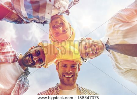 business, building, partnership, construction and people concept - close up of smiling builders and architect in hardhats in circle outdoors