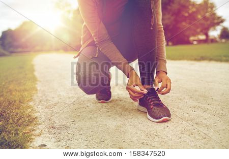 sport, fitness, people and lifestyle concept - close up of woman tying shoelaces outdoors