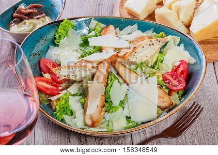 Salad with chicken breast parmesan cheese croutons tomatoes mixed greens lettuce and glass of wine on light wooden background