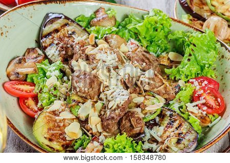 Hot salad with veal mushrooms salad leaves eggplant zucchini tomatoes garnished with grated almonds and Parmesan cheese and glass of wine on wooden background. Healthy food