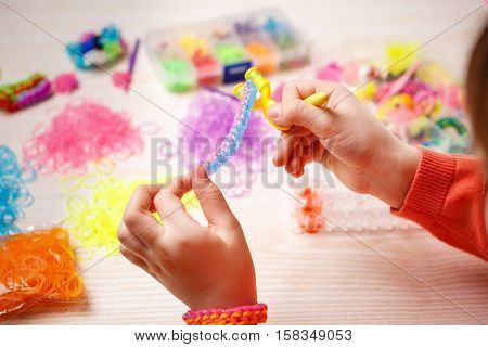 hands weaving of colored rubber band bracelet, closeup, wooden background