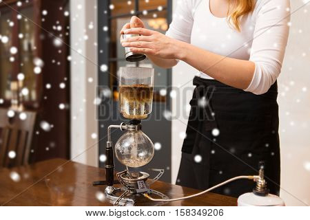 equipment, people and technology concept - close up of woman with pot pouring ground coffee to siphon coffeemaker at cafe bar or restaurant kitchen over snow