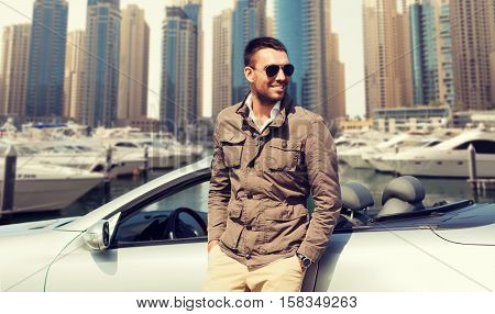 auto business, transport, leisure and people concept - happy man near cabriolet car over dubai city port background