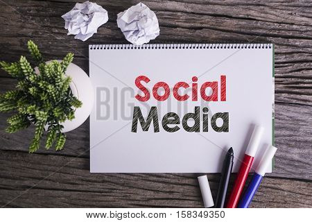Notepad and green plant on wooden background with Social Media word