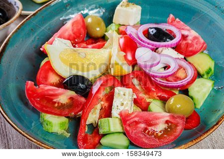 Greek salad of organic vegetables with tomatoes cucumbers red onion olives feta cheese and glass of wine on wooden background. Healthy food
