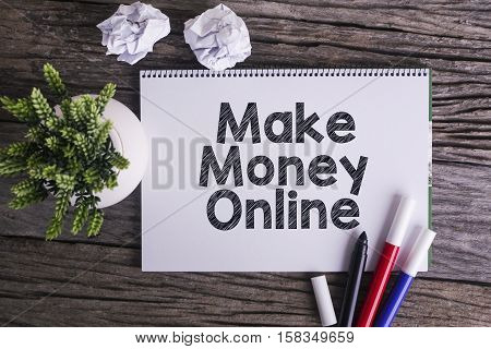Notepad and green plant on wooden background with Make Money Online word