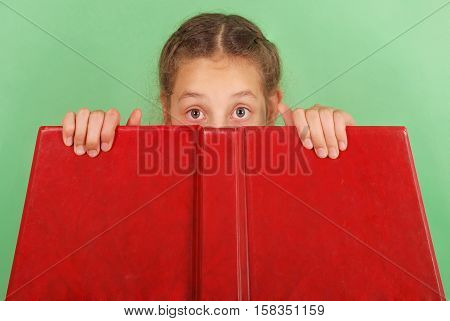 Beautiful school girl peeping from behind her red book isolated on green
