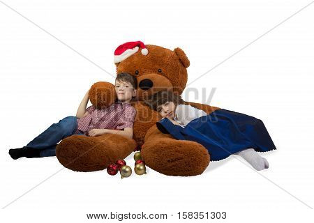 Girl and boy are embracing huge teddy bear with santa's hat on his head on Christmas Eve. Isolated on white background.