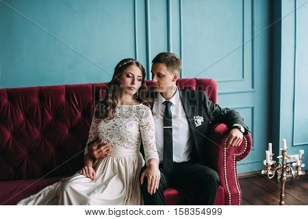 Cute Wedding Couple In The Interior Of A Classic Studio Posing At The Sofa . Hey Kiss And Hug Each O