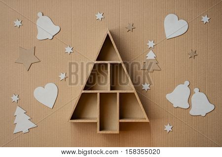 Christmas tree shaped gift box and decorations on cardboard background
