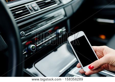 Woman Using White Smartphone In Car.