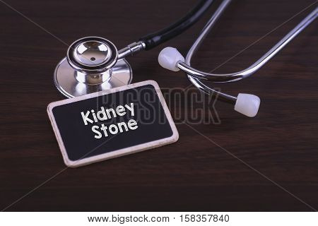 Medical Concept- Kidney Stone words written on label tag with Stethoscope on wood background