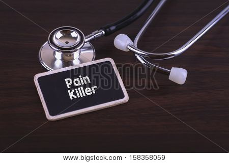 Medical Concept- Pain Killer words written on label tag with Stethoscope on wood background