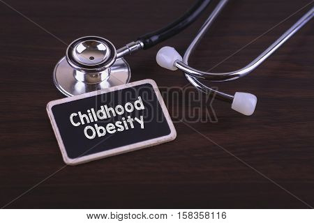 Medical Concept- Childhood Obesity words written on label tag with Stethoscope on wood background