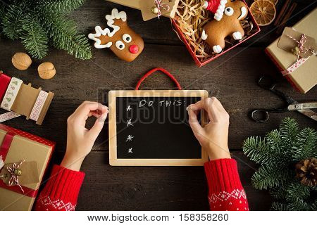 Female writing wish list near christmas gifts.Festive Christmas Card With Chalkboard. Top view.