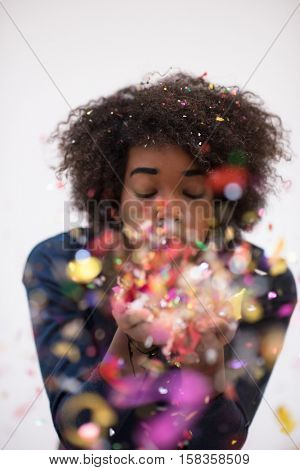 happy young woman celebrating new years eve party while blowing confetti
