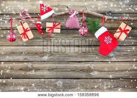 Christmas decoration stocking and gift boxes hanging over rustic wooden background