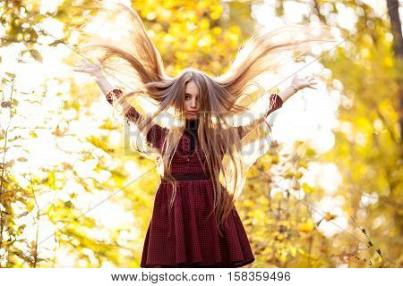 Young girl in a burgundy dress with long hair flying up and raised his hands in the autumn forest day