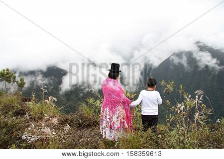 Bolivian mother and child enjoy the view of the mountains, Death road, Yungas region, Bolivia, South America