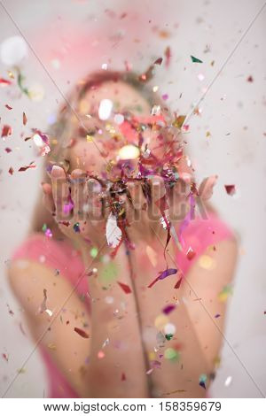 Beautiful  woman blowing confetti in the air party new years eve celebration isolated on white background