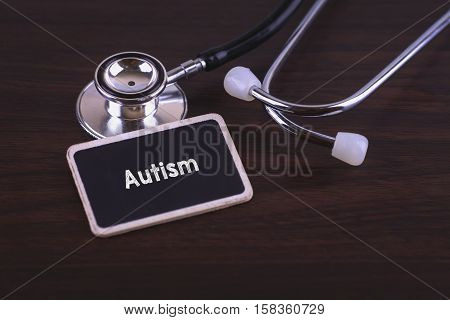 Medical Concept- Autism words written on label tag with Stethoscope on wood background